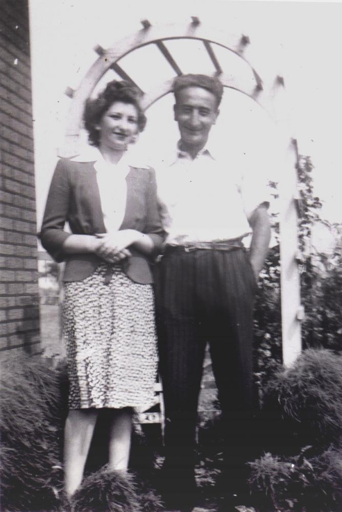 Photo en noir et blanc d'un homme et une femme se tenant ensemble à l'extérieur sous une tonnelle, souriant à la caméra. L'homme a les mains dans les poches.