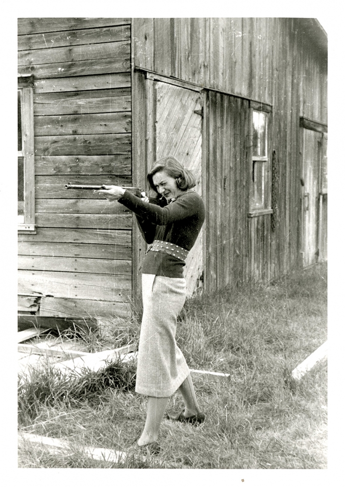 Black-and-white photograph of a woman standing in front of a barn. She holds up a rifle and aims it towards the left of the camera.
