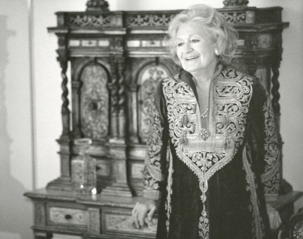 Black-and-white photograph of an elderly woman dressed in an embroidered tunic, leaning against an elaborately carved wooden hutch.