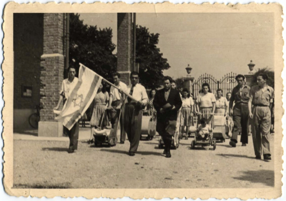 Black-and-white photograph of a parade or march with a large group people walking towards the camera. A man at the front of the crowd carries the flag of Israel, and several women in the background push strollers.
