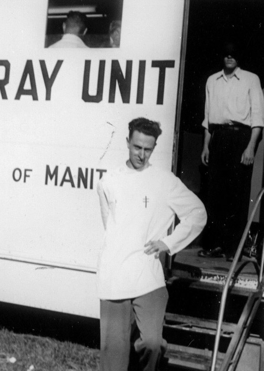 "Black-and-white photograph of a man, standing with a hand on his left hip, in front of a large white truck that reads ""X-RAY UNIT"" on its side. A man stands behind him inside the entrance of the truck with his face covered by shadow."