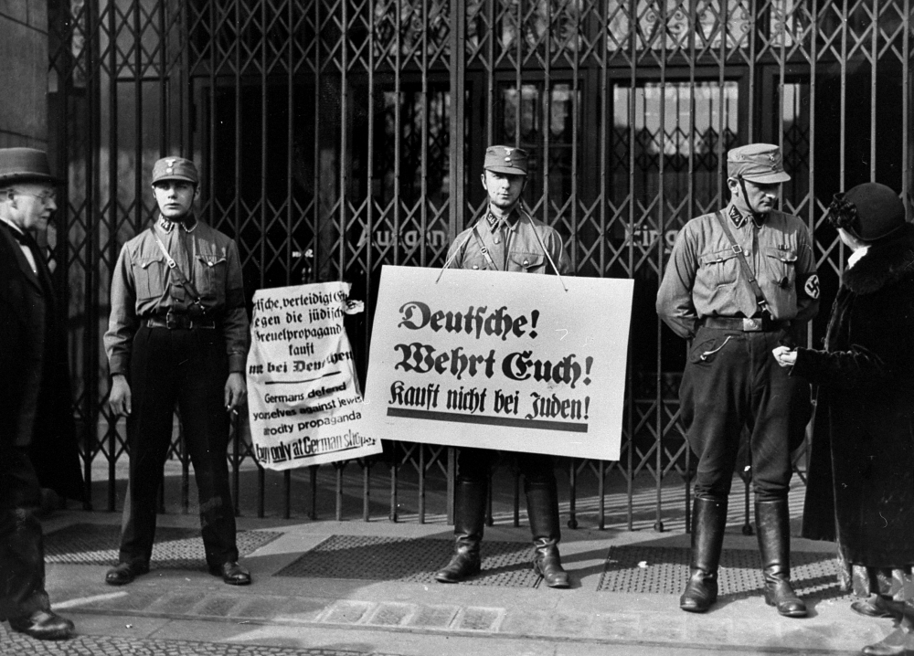 Black-and-white photograph of three men in military uniforms, standing in front of a closed storefront that has iron gates. Two of the hold up signs written in German. The other soldier is in discussion with a civilian.
