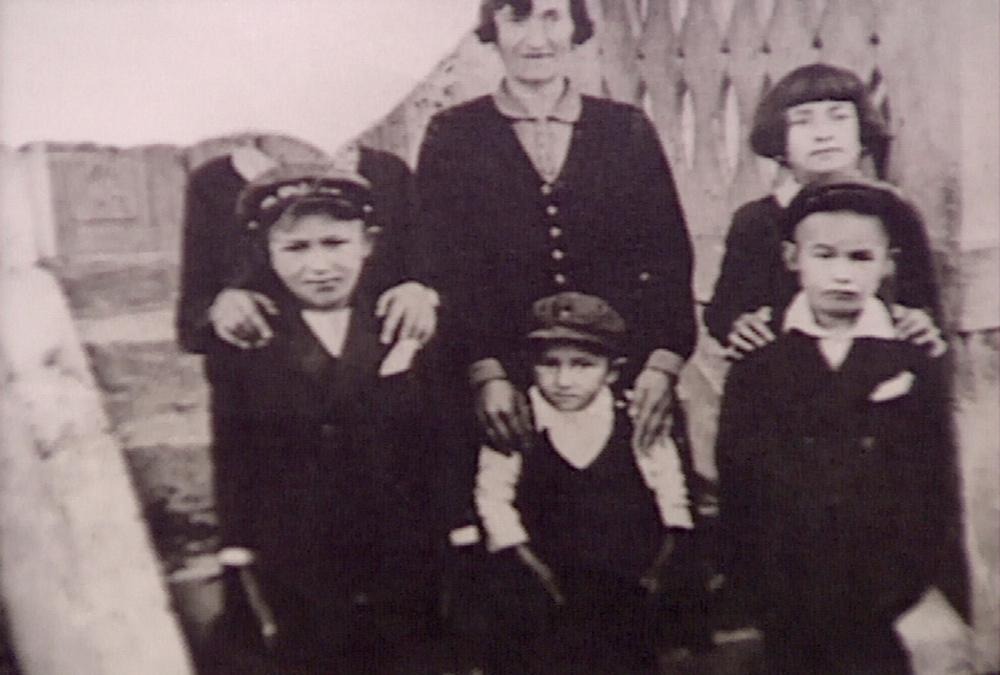 Black-and-white photograph of a woman with five children standing together, the three in the back row putting their hands on their family members' shoulders in front. The photograph is torn in the top-left corner so that the face of the person standing in the top left is not visible.