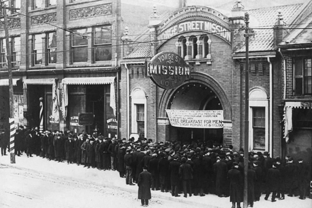 Photo en noir et blanc d'une scène extérieure d'une rue. Un groupe de personnes se tiennent en ligne à l'extérieur d'un édifice.
