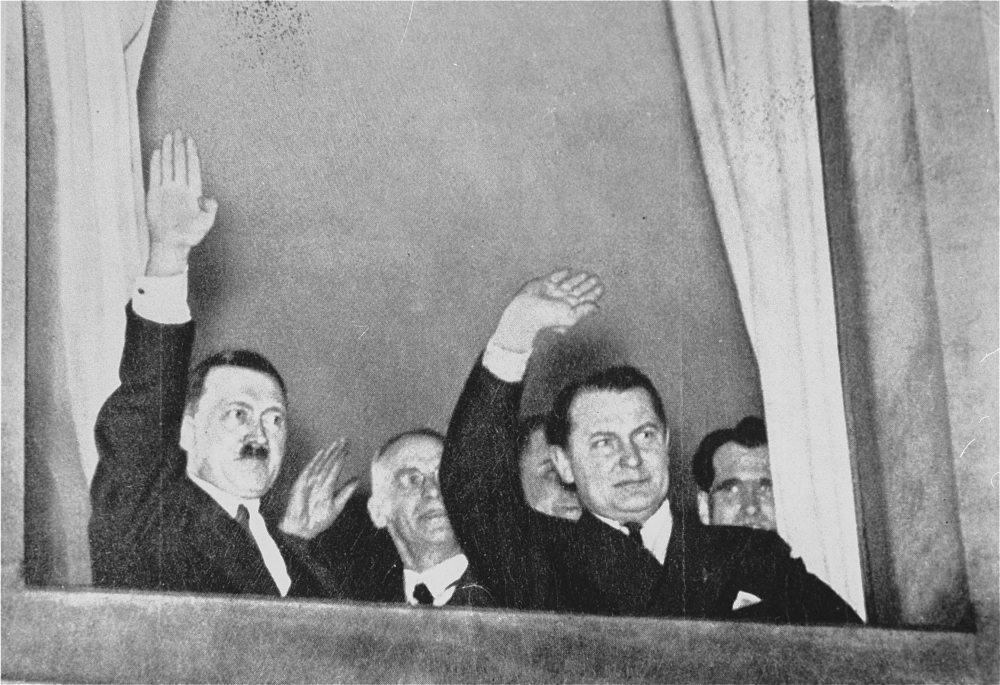 Black-and-white photograph of two men in waving out a window. The photograph is taken from below, outside. The man on the left has a moustache, and there are men behind them in the background.