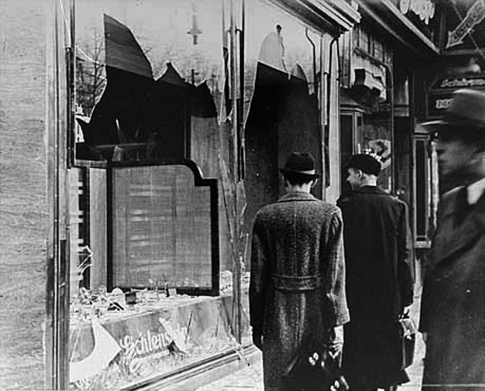 Black-and-white photograph of three men in hats and jackets, standing on a sidewalk and looking at two shattered storefront windows. Two men have their back to the camera.