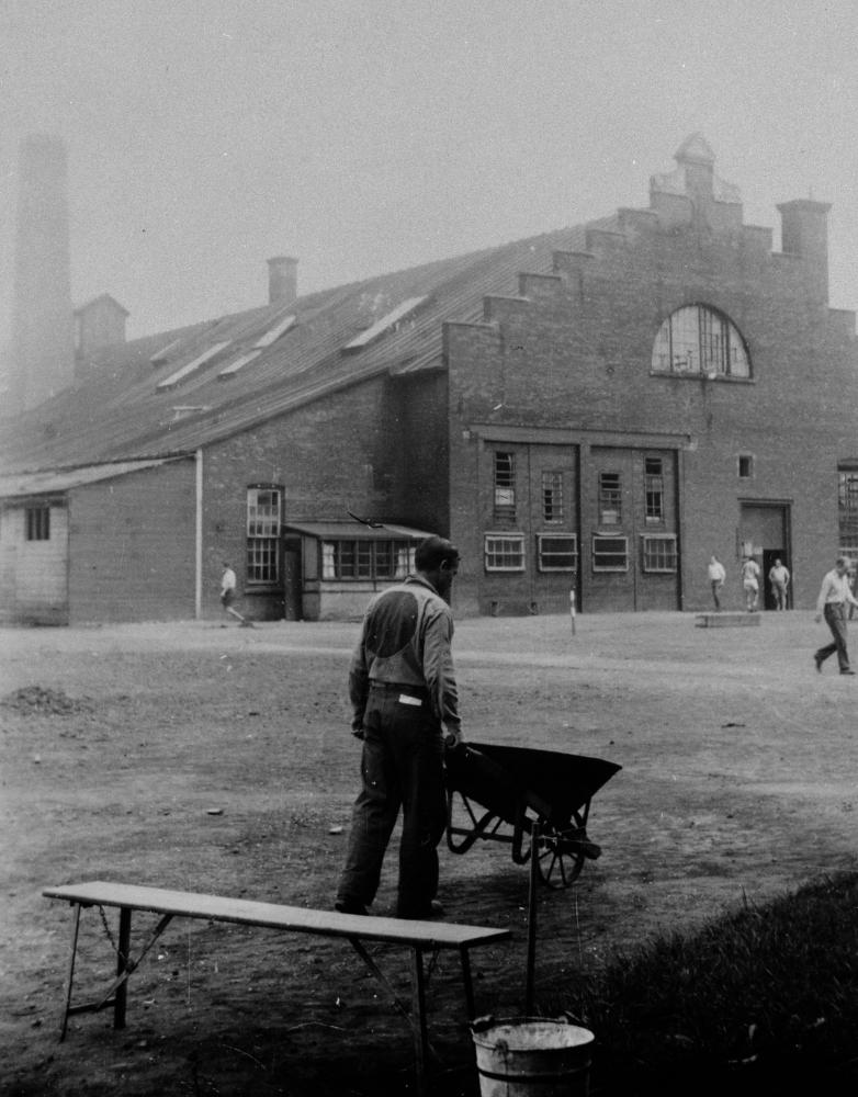 Photo en noir et blanc d'un homme, se tenant dos à la caméra, pousse une brouette dans une cours. Il y a un banc en avant-plan et un bâtiment en arrière-plan. L'homme porte un uniforme avec un grand cercle dans le dos.