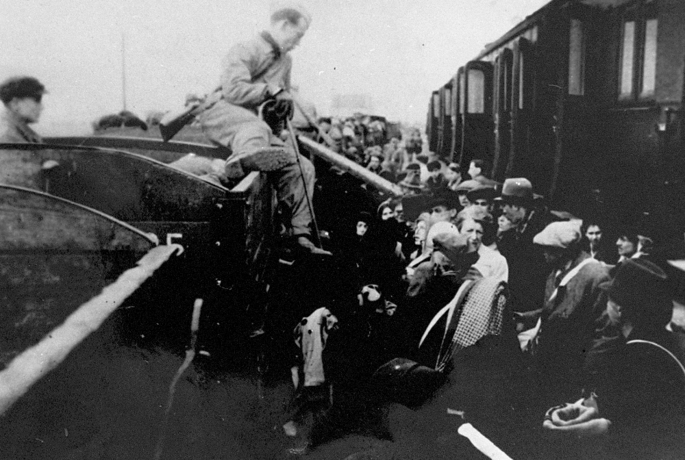 Black-and-white photograph of a man sitting on the edge of a train car, holding a cane, and looking onto a platform full of people.
