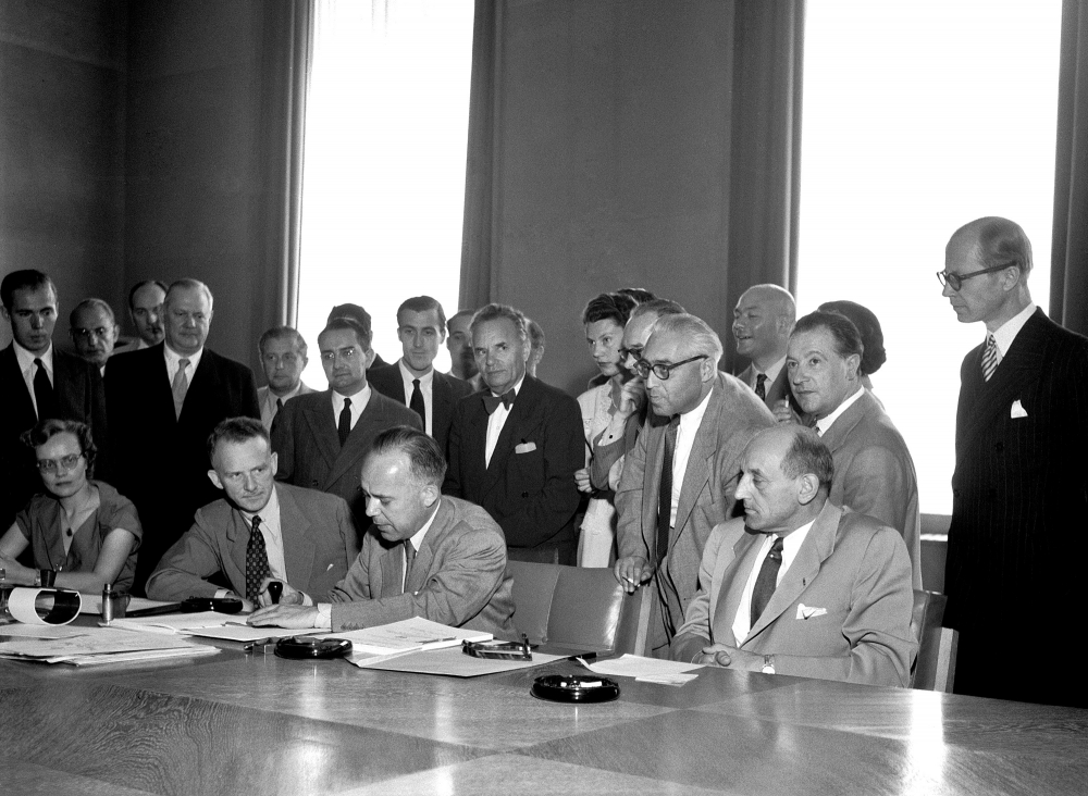 Black-and-white photograph of a group of about 25 people gathered together behind a large table in a conference room. Four men sit at the table, and one man is signing a document. The other people stand behind.