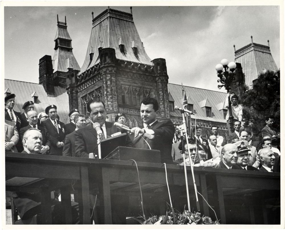 Photo en noir et blanc d'un homme en costume parlant dans deux microphones à un podium à l'extérieur. Il est entouré d'un groupe de gens, certains sont assis, un grand édifice est à l'arrière-plan.