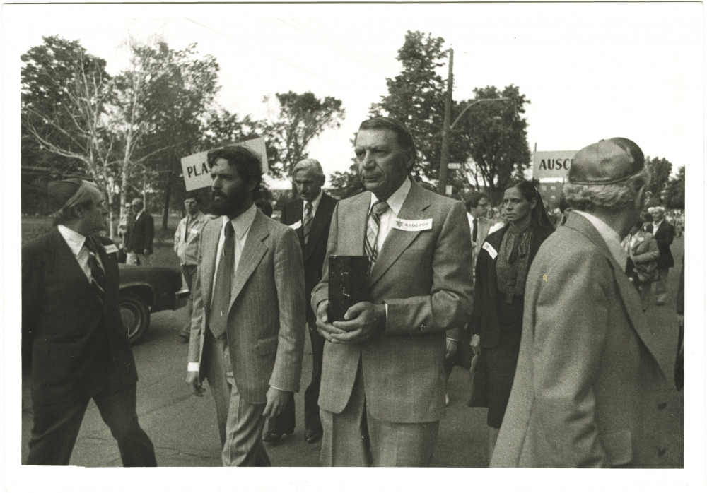 Black-and-white photograph of four men leading a march outdoors. The man in the centre is carrying a rectangular box. A group of people follows them in the background.