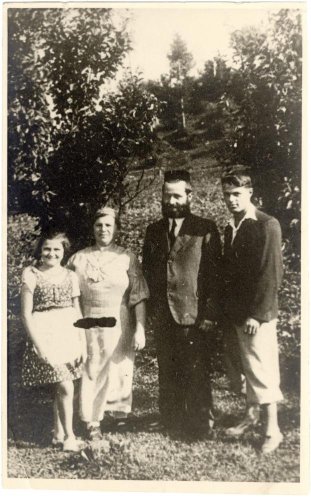 Photo en noir et blanc d'un groupe de quatre personnes debout à l'extérieur, avec des arbres en arrière-plan.