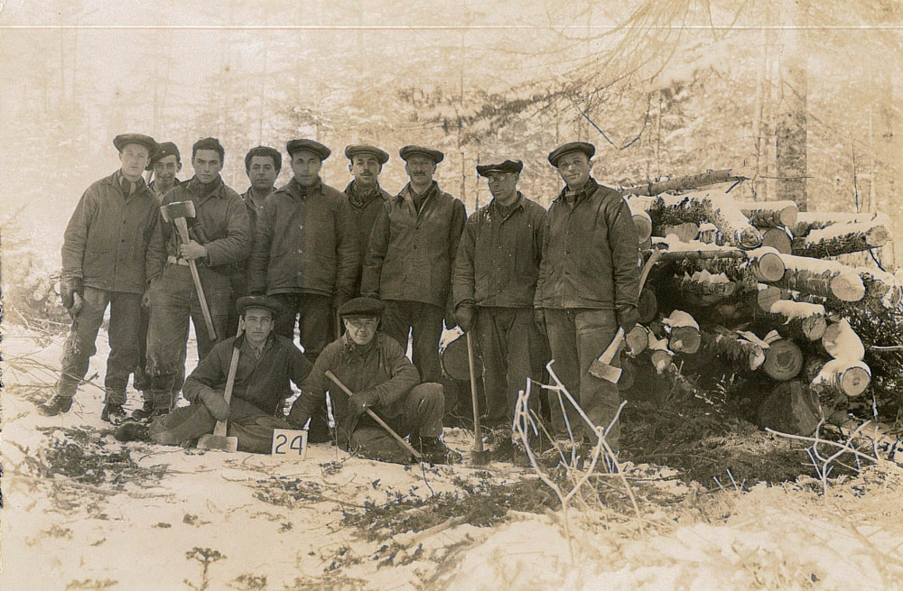 Black-and-white photograph of a group of eleven men posing together for a photograph in the woods. Some of the men are holding axes. They are grouped together in front of a pile of wood, wearing matching outdoor uniforms.