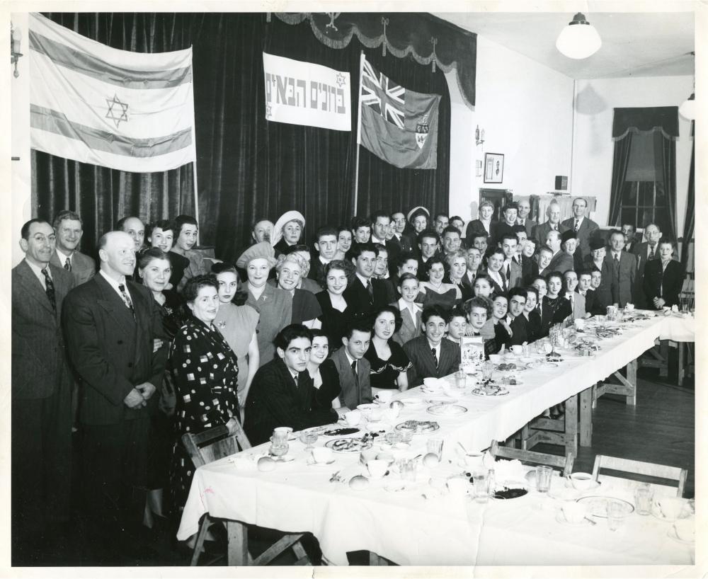 Photo en noir et blanc d'un grand groupe d'environ 70 personnes souriant pour une photo de groupe dans une salle. Le groupe est installé derrière une grande table sur laquelle sont disposés des plats et de la nourriture, et deux drapeaux sont accrochés sur des rideaux en arrière-plan.