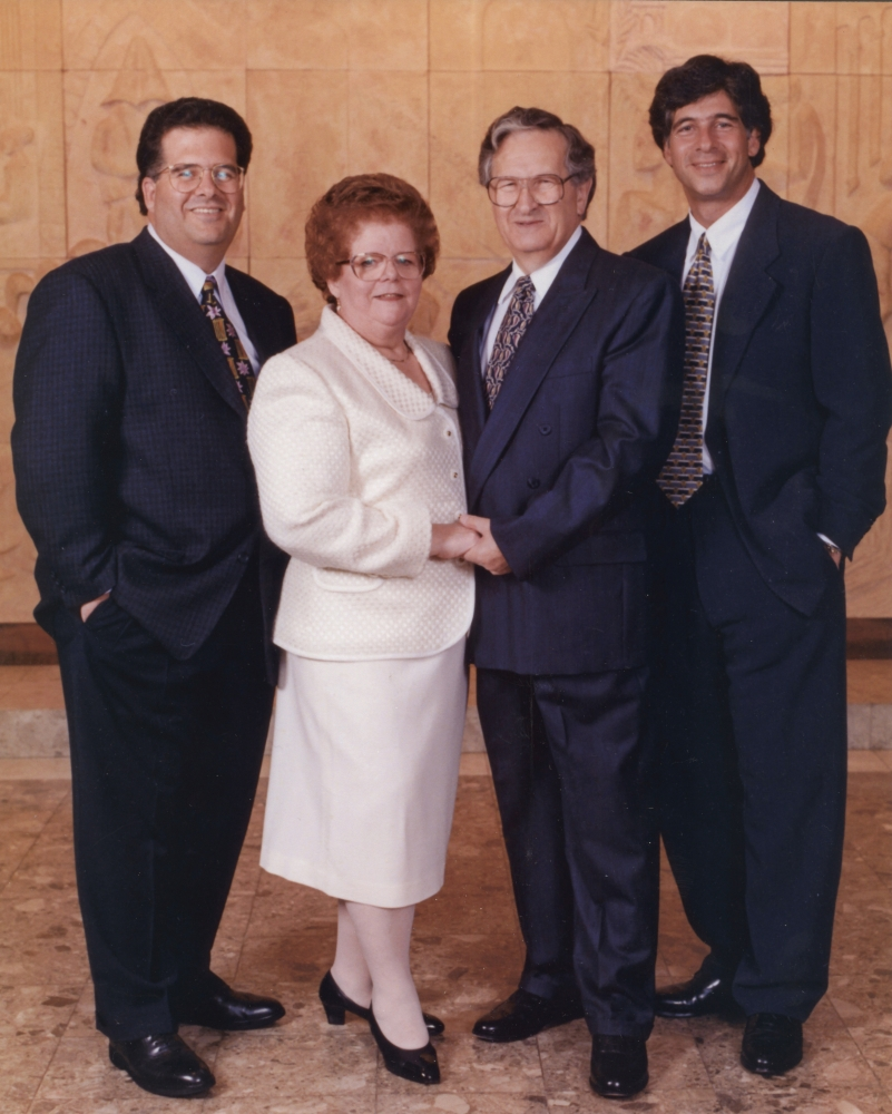 Colour studio photograph of a group of four adults standing together and smiling at the camera. The couple in the middle is elderly, and the woman wears a white jacket and skirt. The three men wear suits.