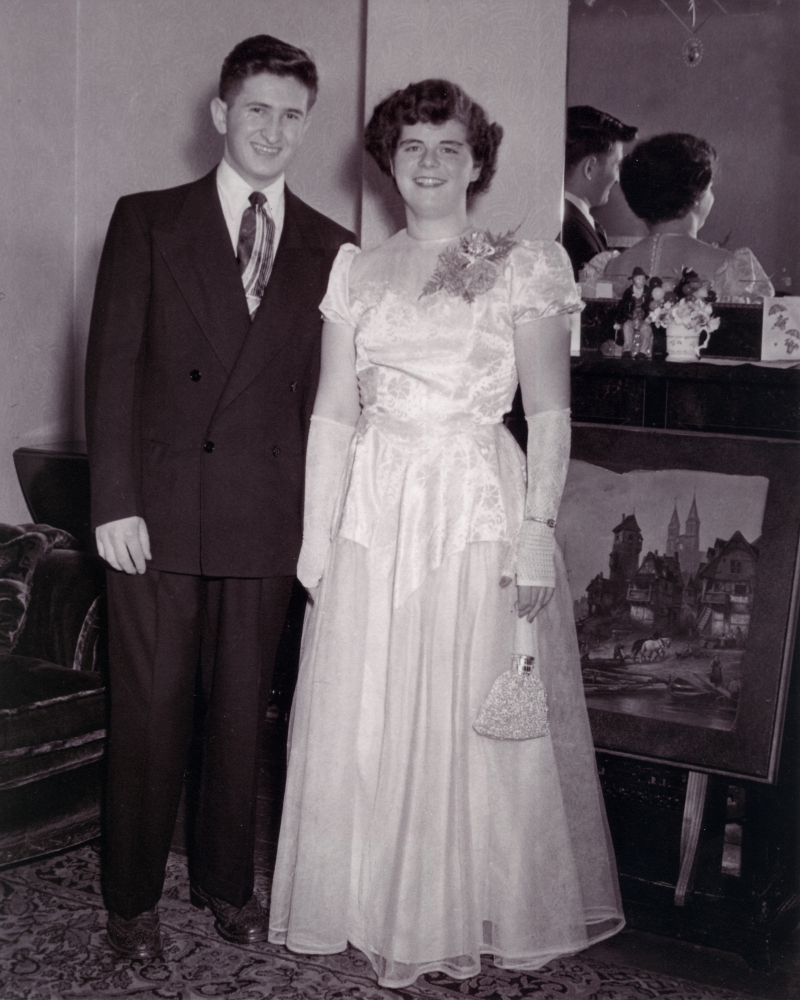 Black-and-white photograph of a young man and woman standing and smiling together indoors, in front of a mirror. The woman wears a formal long, light-coloured gown with a purse, and the man wears a suit.
