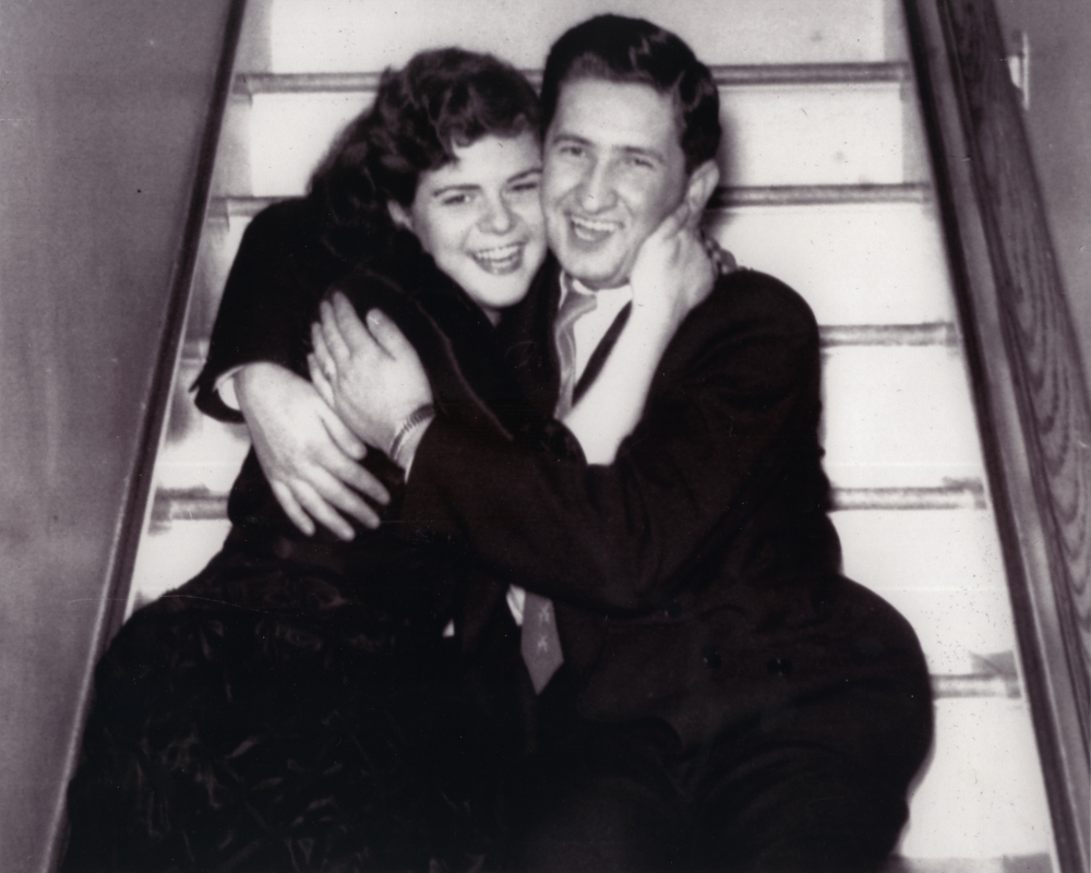 Black-and-white photograph of a young couple smiling and sitting in each other's arms on a stairwell.