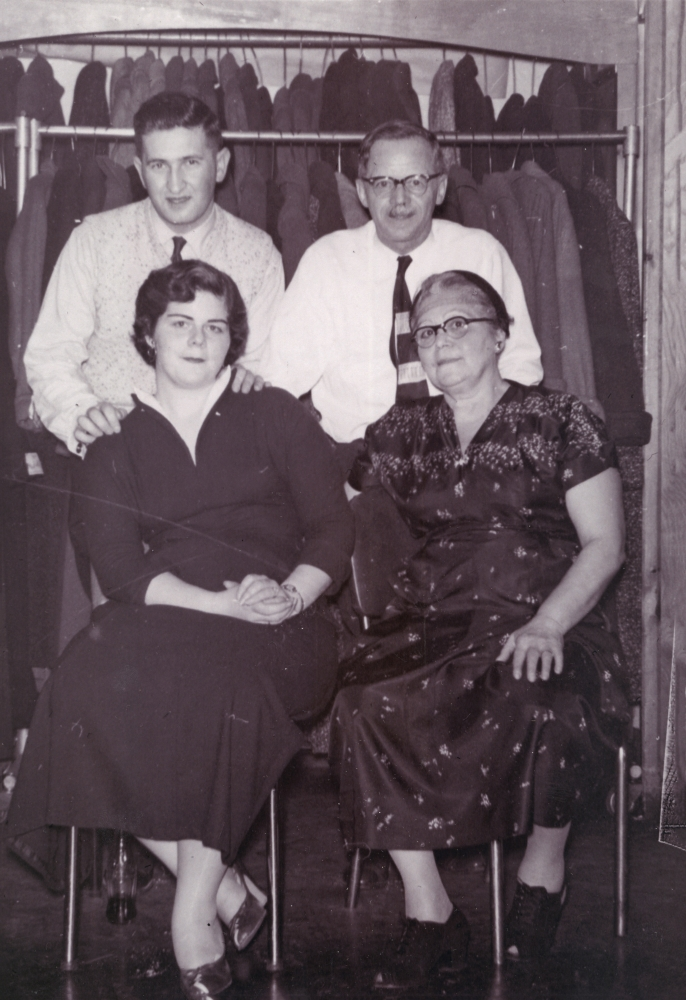 Black-and-white photograph of two men standing behind two women, who are sitting on chairs. The couple on the right appears to be older than the other couple. Both men wear shirts and ties, and the women wear dresses.
