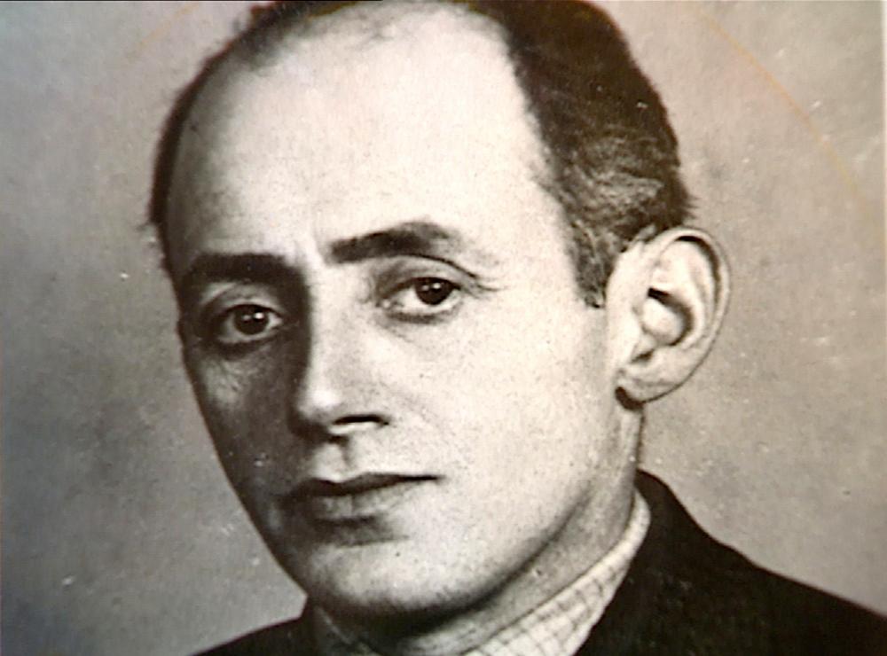 Portrait photographique du visage d'un homme qui regarde la caméra. Ses cheveux de couleur foncée sont coiffés vers l'arrière et il semble qu'il porte un complet.