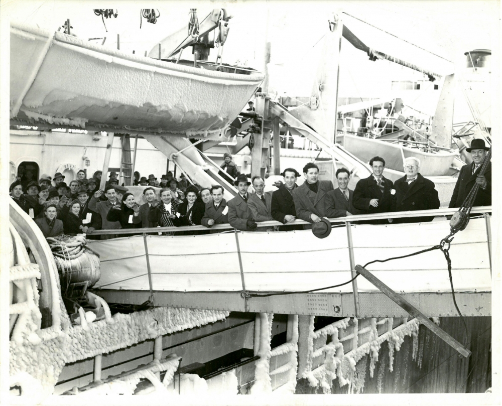 Black-and-white photograph of a group of 15 people, wearing coats and hats, smiling and waving at the camera from the gangway of a ship. Several more people wait to disembark the ship. A lifeboat is suspended in the top-left corner with ice frozen to its sides.