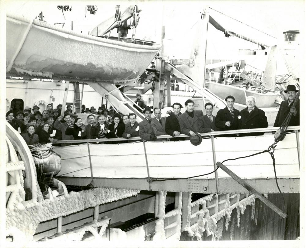 Photo en noir et blanc d'un groupe de 15 personnes, portant manteaux et chapeaux, souriant et saluant la caméra depuis la passerelle d'un navire. Plusieurs autres personnes attendent leur tour pour débarquer du navire. Un bateau de sauvetage dont les côtés sont glacés est suspendu dans le coin supérieur gauche.