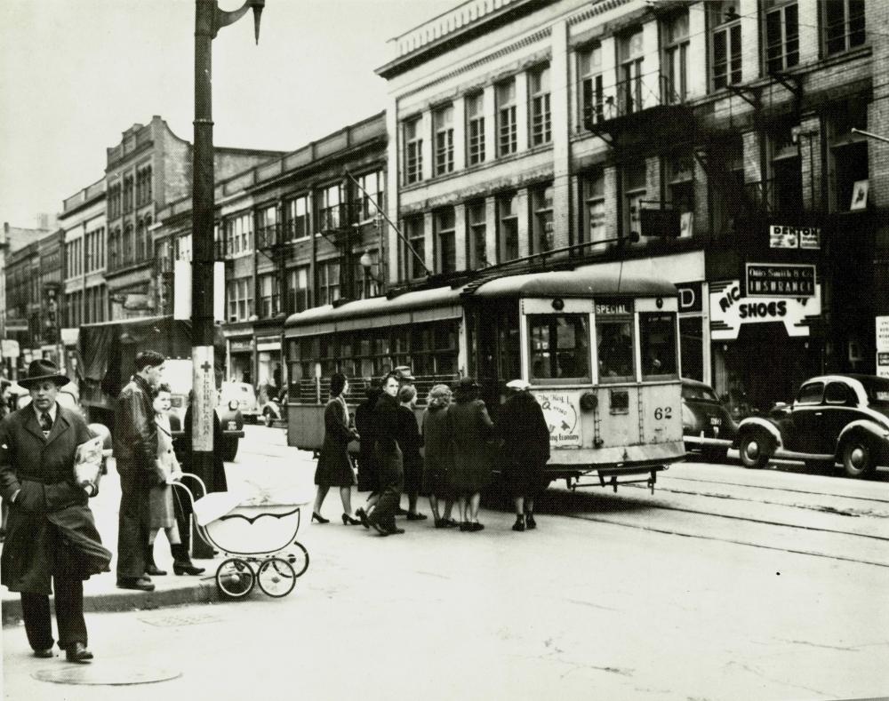 Photo en noir et blanc d'une scène d'une, prise au niveau de la rue. Un groupe de personnes attendent pour embarquer dans un tramway stationné dans la rue.