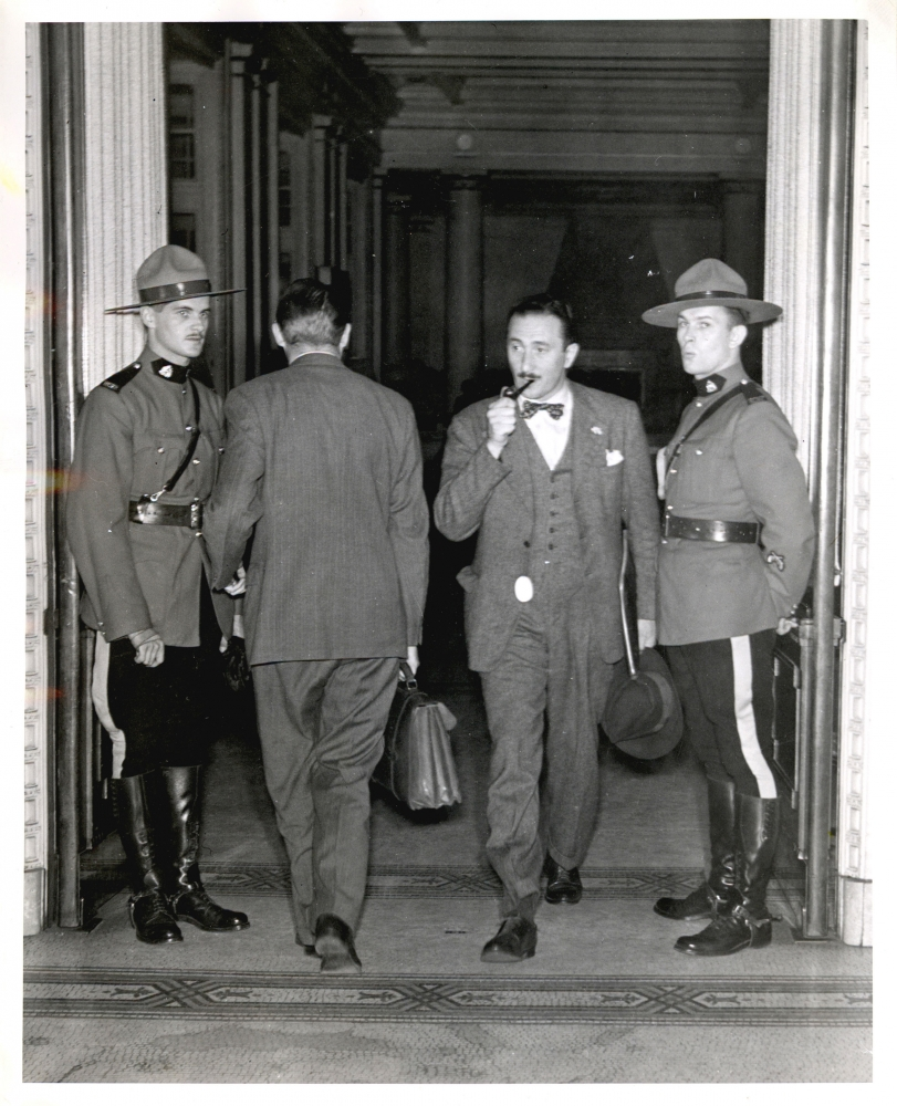Black-and-white photograph of four men in a large doorway. One man, second from the right, is exiting the room with a briefcase and pipe in his mouth. The man to his left is entering the room. The two men on either side are dressed in RCMP uniforms and look towards the camera.