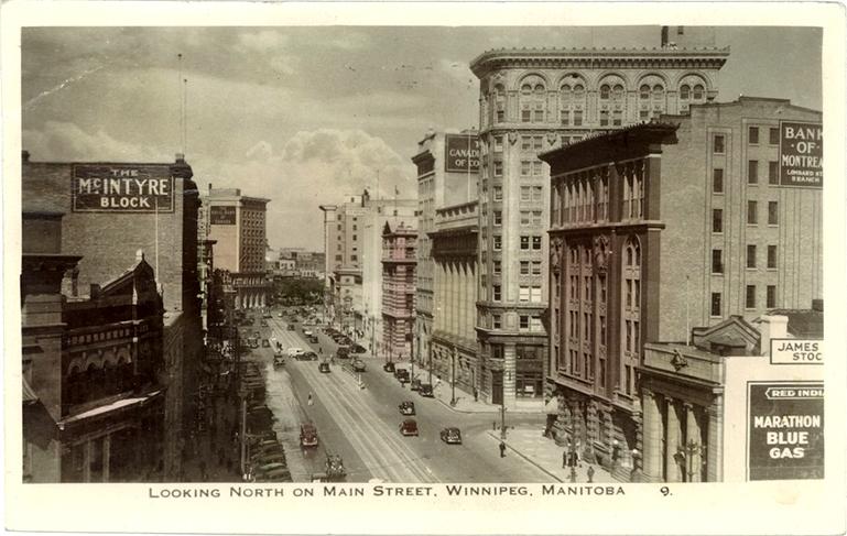 Photo en noir et blanc de bâtiments légèrement colorés en jaune et rose, représentant la vue d'une rue d'une ville où il y a des édifices en brique et des vitrines de commerces. Il y a des affiches sur trois bâtiments pour The McIntyre Block, Marathon Blue Gas et Bank of Montreal.