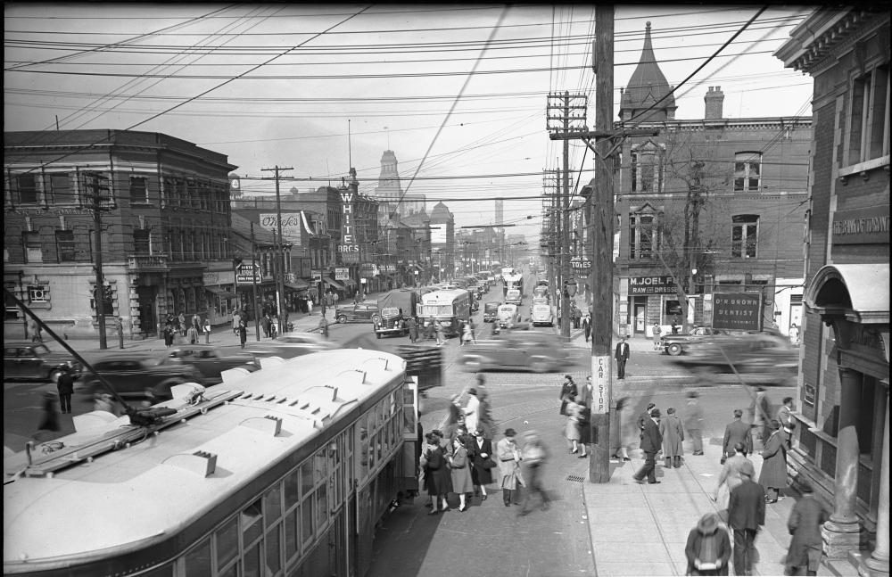 Photo en noir et blanc de l'intersection d'une rue achalandée. Des piétons montent à bord d'un tramway dans le coin inférieur gauche, et des fils électriques traversant les airs sont visibles dans la partie supérieure de la photo.
