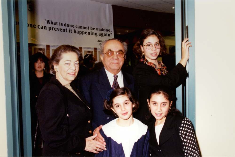 Colour photograph of an elderly man and woman, standing together indoors with a woman and two young girls. The family is formally dressed, with the girls wearing blouses and the man in a suit.