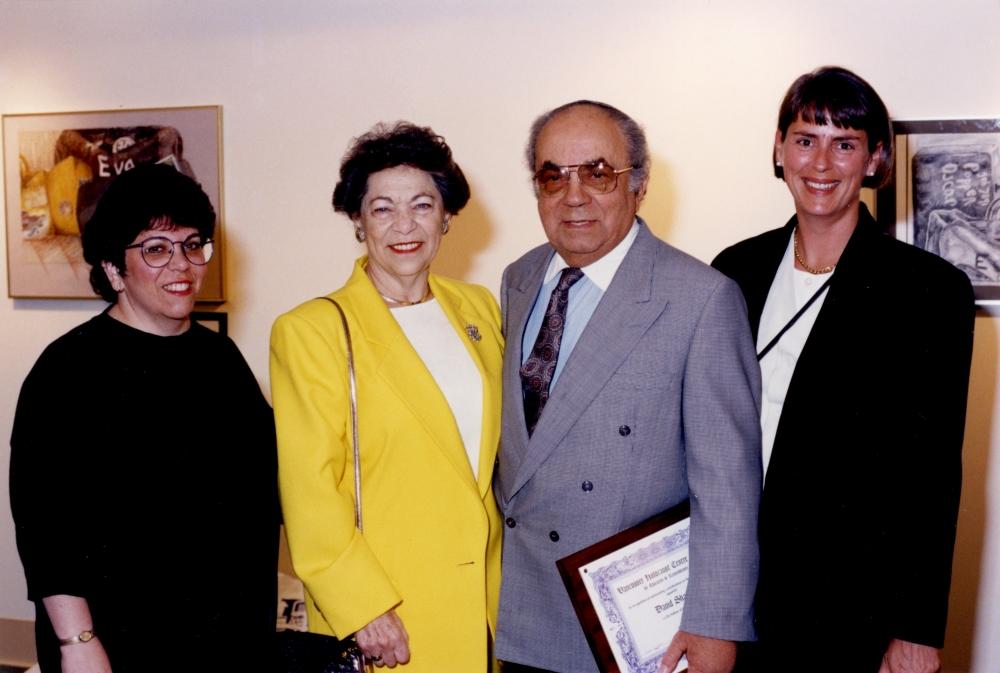 Photo en couleur d'un homme et d'une femme âgés se tenant entre deux autres femmes. Ils sourient tous les quatre à la caméra. L'homme porte un complet et tient un document encadré.