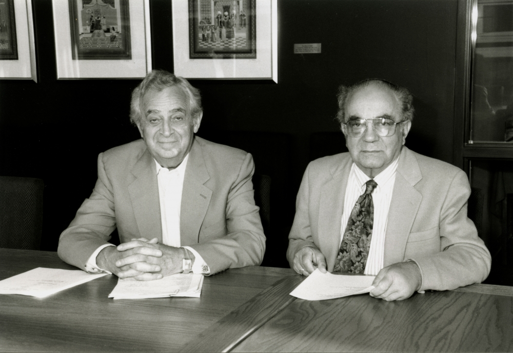 Black-and-white photograph of two elderly men sitting at a table with papers in front of them. The men wear suit jackets, one them wearing a tie, and there are three framed artworks hung on a wall in the background.
