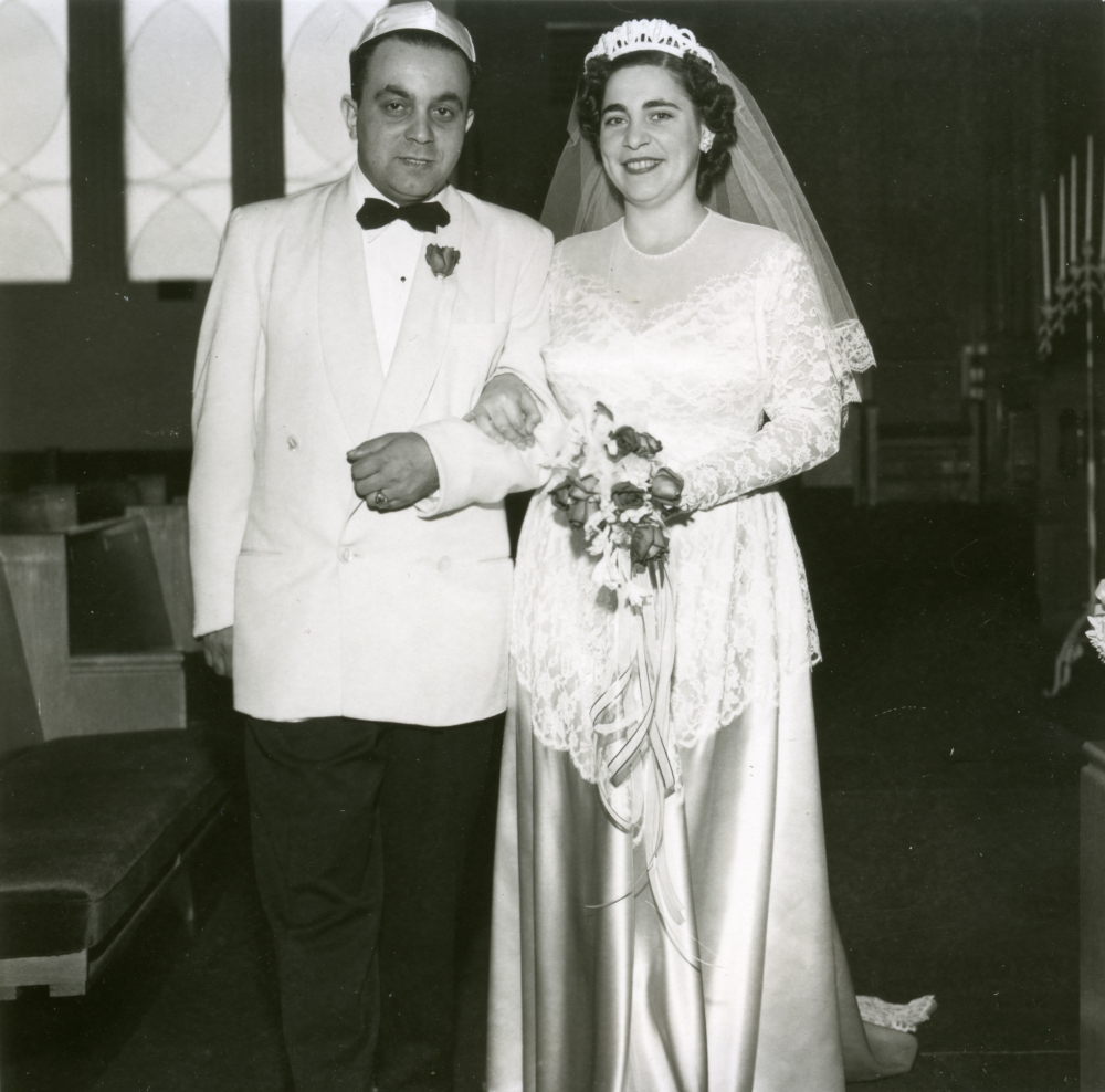 Black-and-white photograph of a man and woman, standing together arm-in-arm indoors. The couple appears to be celebrating their wedding day. The man wears a suit with a light-coloured jacket and bowtie, and the woman wears a long white gown with silk skirt, a veil, and holds a bouquet of flowers.