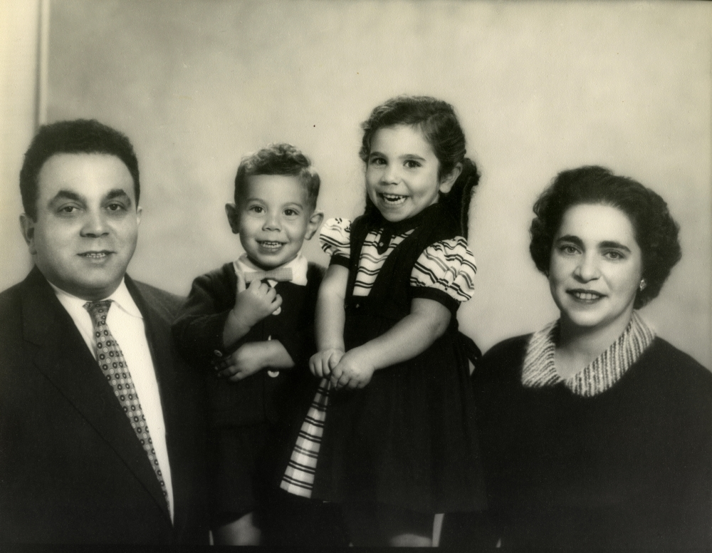 Black-and-white photograph of a man and woman with two young children, all smiling at the camera.