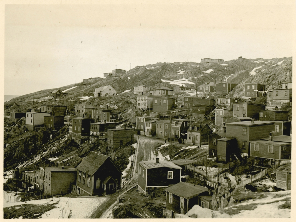 Black-and-white photograph of small residential buildings in a hillside town or village. There is snow on the ground and it appears to be winter.