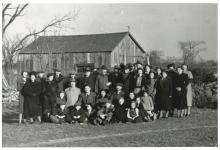 Photo en noir et blanc d'un grand groupe d'environ 35 hommes, femmes et enfants, habillés de manteaux d'hiver et de chapeaux, assemblés à l'extérieur sur une pelouse. Il y a une grange à l'arrière-plan derrière le groupe.