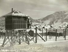 Black-and-white photograph of a guard standing at attention in his barracks, surrounded by barbed wire. Rows of buildings are in the background, with snow-covered hills in the distance. There is snow on the ground.