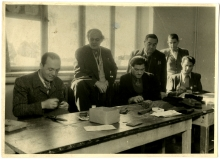 Photo en noir et blanc d'un groupe de six hommes, trois se tenant debout et trois étant asss à une table. Les trois hommes debout regardent les trois qui sont assis pendant qu'ils cousent à une table avec du fil et une aiguille.