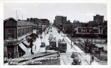 Photo en noir et blanc d'une scène d'une rue, prise en hauteur. Une large rue où circulent des piétons sur les trottoirs, il y a des vitrines de commerce de chaque côté, et trois tramways qui circulent au centre de la rue.