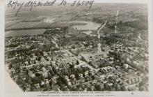 Photo aérienne en noir et blanc d'une ville où une rivière peut être aperçue au loin. Un texte est manuscrit dans le coin supérieur gauche de la photo.