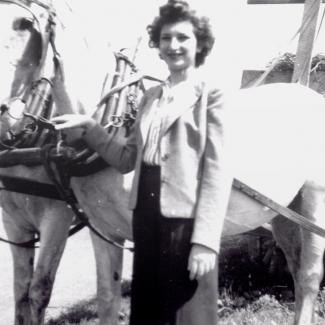 Photo en noir et blanc d'une femme aux cheveux bruns foncés, se tenant à l'extérieur auprès de deux chevaux blanc attachés à une voiture ou un charriot. Elle tient les rênes des cheveux d'une main.