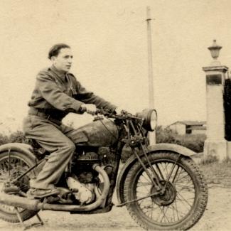 Photo en noir et blanc d'un jeune homme sur une motocyclette, regardant vers la droite de la caméra. Il y a une haie derrière lui et un bâtiment en arrière-plan.