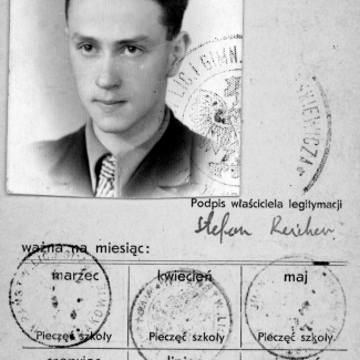 Black-and-white document with a photograph in top-left corner of a young man with combed-back hair, wearing a suit and tie. The document contains Polish writing, four stamps, and a signature.