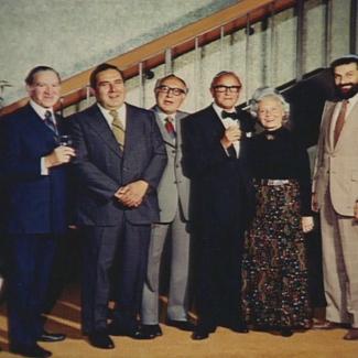 Photo en couleur d'un groupe de huit personnes se tenant debout en ligne et souriant à la caméra. Les sept hommes portent des complets et la femme du groupe porte un robe longue.