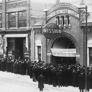 Black-and-white photograph of an outdoor street scene. A group of people are lined up outside a building.