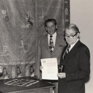 Black-and-white photograph depicting two men in suits standing around a table indoors. The man on the right is holding a document and a small urn.