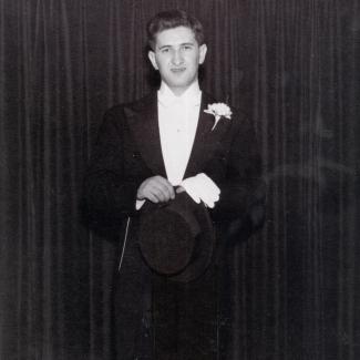 Photo en noir et blanc d'un jeune homme portant un tuxedo , se tenant devant un rideau de couleur foncée.