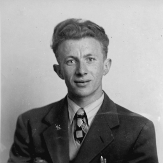 Black-and-white square-shaped identity photograph of a young man, wearing a suit, and smiling at the camera.