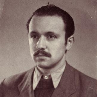 Photo de couleur sépia d'un homme, prise à partir de la potrine, regardant vers la gauche de la caméra. Il porte un complet et une cravate et ses cheveux sont coiffés vers l'arrière. Il porte une moustache.