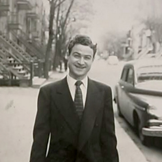 Black-and-white photograph of a man standing outside on a sidewalk, wearing a suit and smiling at the camera. The street behind him has a vintage car parked on the right, as well as trees, balconies, and stairwells leading up to apartments.